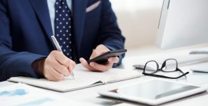 Cropped image of businessman checking messages in smartphone and taking notes in planner
